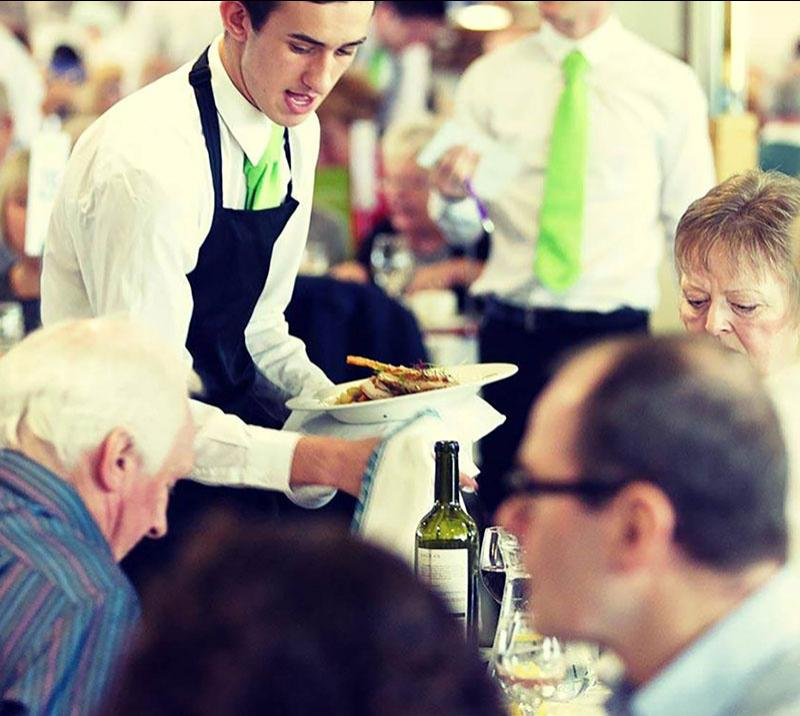 A member of waiting staff delivers a course of food to eager diners.