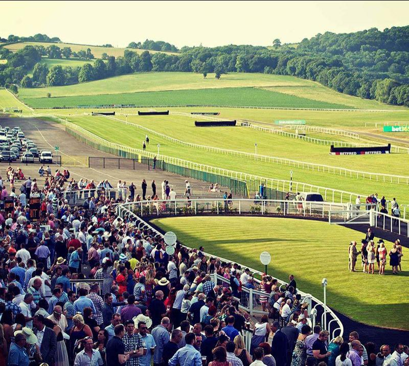 A view across the crowd in the grandstand and the green turf track at Chepstow Racecourse.