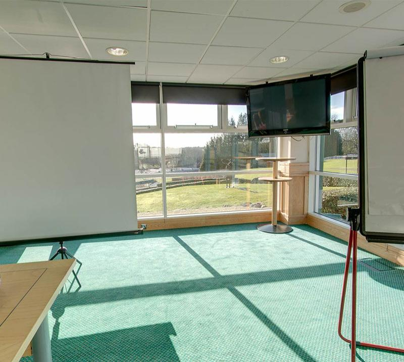 A smaller well lit room with whiteboards and a TV screen mounted from the roof.