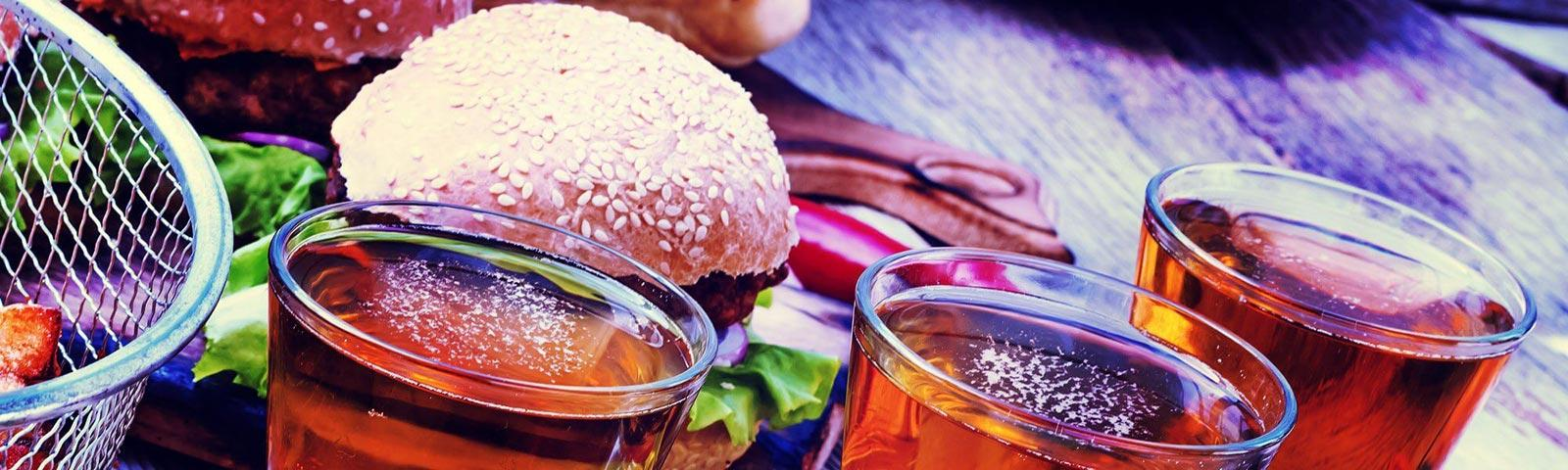 Close up on on a burger on a plate and glasses filled with a drink.