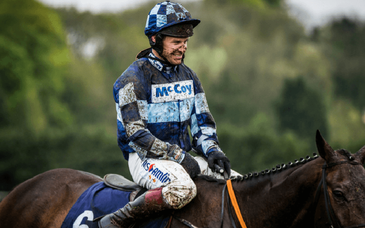 Champion Jockey Richard Johnson sat on his horse covered in mud at the end of a race.