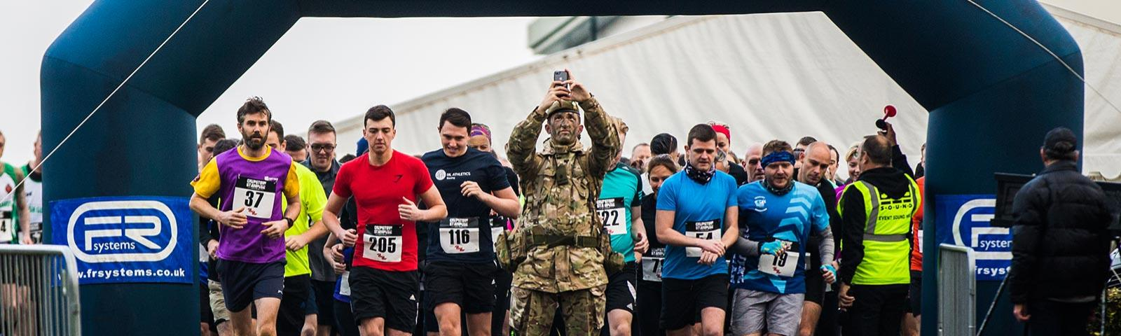 A soldier in camouflage takes a selfie as the stamped gets underway with lots of other competitors in standard running attire