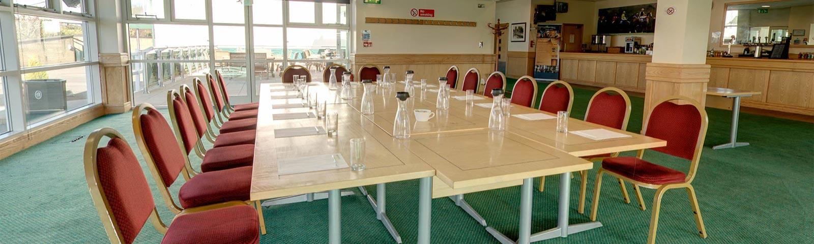 A set of tables joined together in a boardroom style within the Owners and Trainers Suite at Chepstow Racecourse.