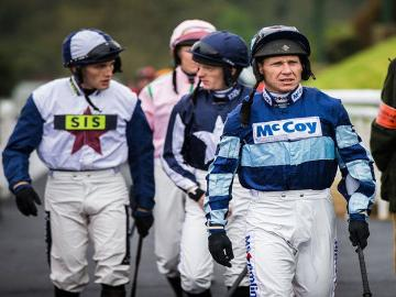 A group of Jockeys walk towards their meeting point