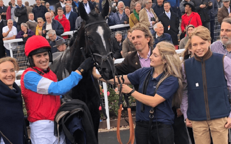 A winning team celebrate with their racehorse